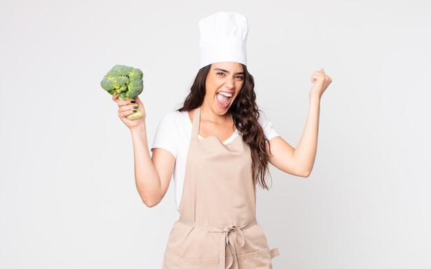Красивая женщина в шоке, смеется и празднует успех в фартуке и держит брокколи