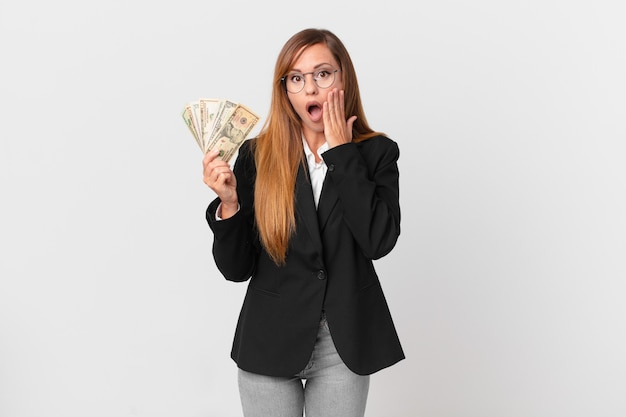 Pretty woman feeling shocked and scared. business and dollars concept