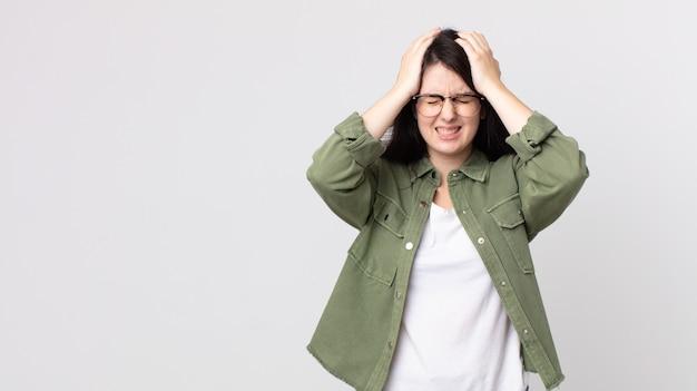 ストレスと不安を感じ、落ち込んで、頭痛で欲求不満を感じ、両手を頭に上げているきれいな女性