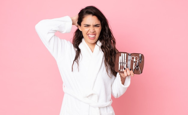 Симпатичная женщина чувствует стресс, тревогу или страх, с руками за голову и держащей косметичку с инструментами для ногтей