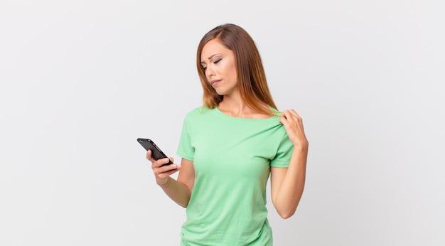 Красивая женщина чувствует стресс, тревогу, усталость и разочарование и использует смартфон