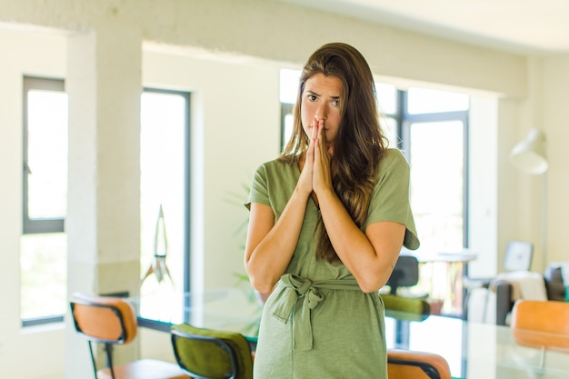 Симпатичная женщина обеспокоена, полна надежд и религиозна, верно молится со сжатыми ладонями, умоляя о прощении