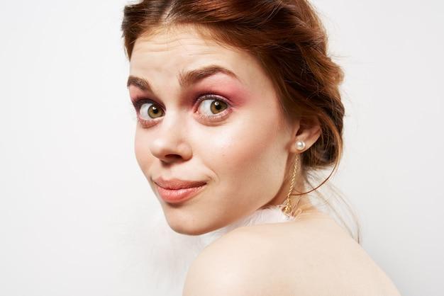 예쁜 여자 솜 털 귀걸이 벌거 벗은 어깨 근접 촬영 밝은 화장
