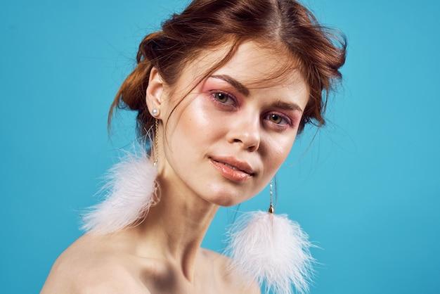 예쁜 여자 솜 털 귀걸이 밝은 메이크업 파란색 배경 패션