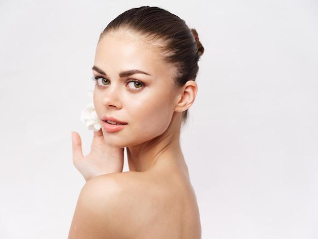油性の肩の化粧品のきれいな肌の明るい背景のきれいな女性