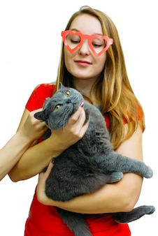 Pretty woman in funny paper glasses with a grey british shorthair cat in her hands, isolated on white.
