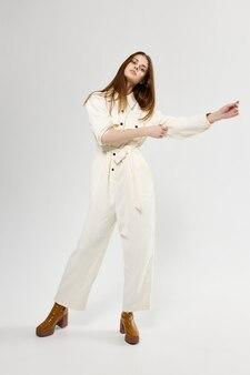 白いジャンプスーツのファッションで彼女の手で身振りで示すきれいな女性