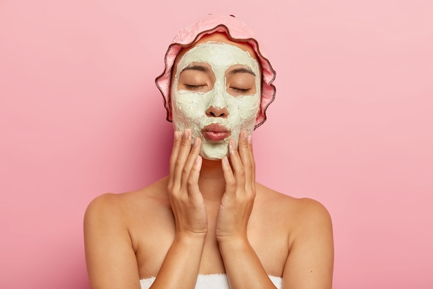 Pretty woman gets beauty treatments, keeps eyes closed, lips folded, has calm gentle expression, applies facial clay mask, stands against pink wall. anti aging procedure