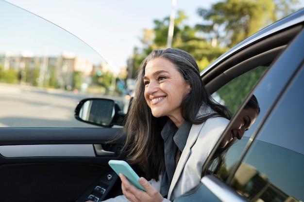Smarpthone幸せな笑顔で車から降りるきれいな女性