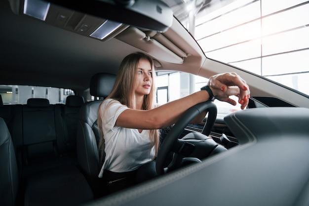 Хорошенькая женщина. девушка в современной машине в салоне. днем в помещении. покупка нового автомобиля.