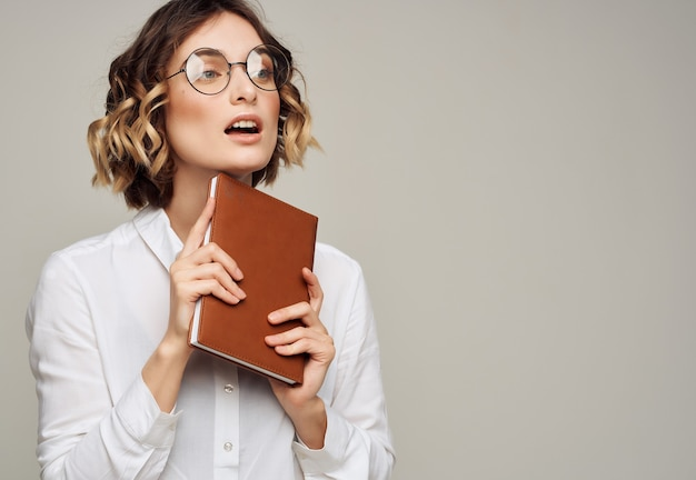 Pretty woman in glasses with book elegant style for professionals studio. high quality photo