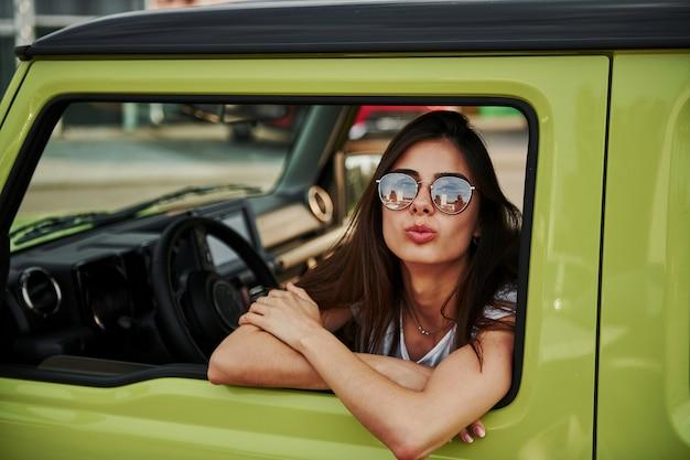 Pretty woman in the green modern car posing