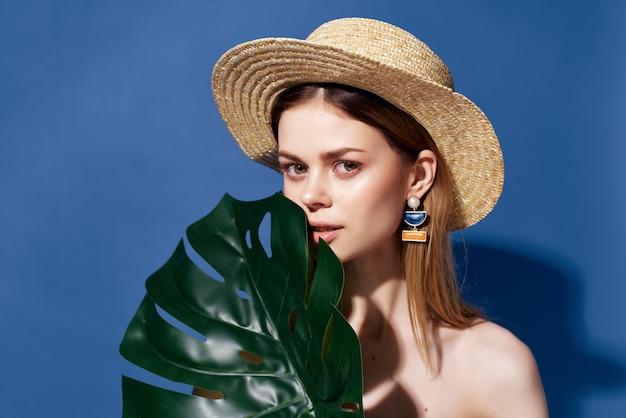 きれいな女性の緑のヤシの葉が青い背景をポーズします。高品質の写真