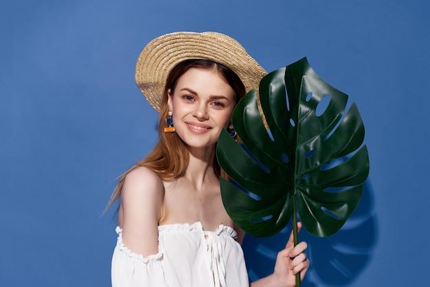 きれいな女性の緑のヤシの葉のポーズのトリミングされたビュー。高品質の写真