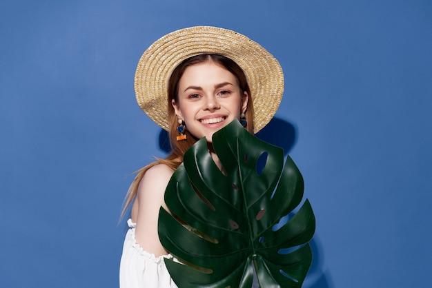 きれいな女性の緑のヤシの葉のポーズのトリミングされたビュー