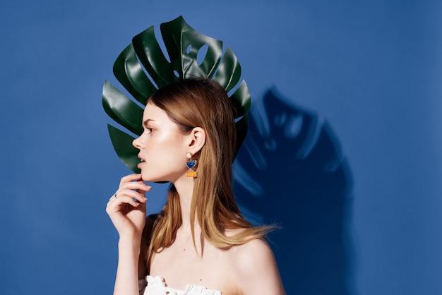 感情的なライフスタイルをポーズするきれいな女性の緑のヤシの葉
