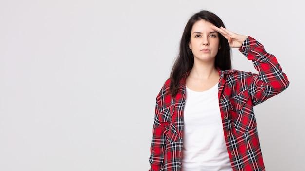 존경을 표시하는 명예와 애국심의 행위에서 군사 경례와 함께 카메라를 인사하는 예쁜 여자