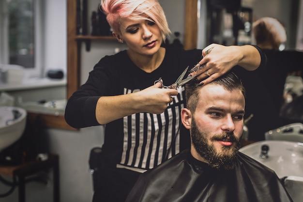 Pretty woman grooming hair of man