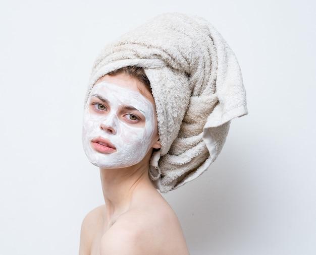 Красивая женщина, уход за белой маской для лица и полотенцем на голове. фото высокого качества
