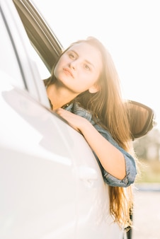Pretty woman hanging out of car window