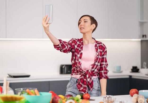 格子縞のシャツを着て新鮮なサラダを調理しながらキッチンでスマートフォンを使用して自分撮りを幸せに取っているきれいな女性