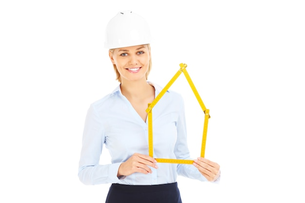 A pretty woman in a hard hat showing a house over white background