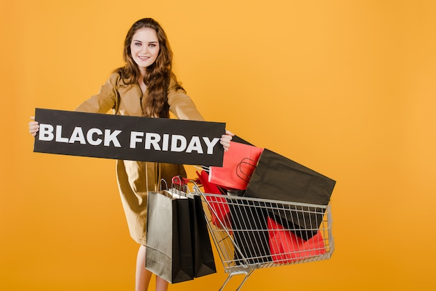 Pretty woman has black friday sign with cart full of shopping bags and signal tape isolated over yellow