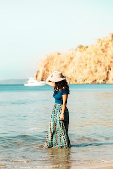 Pretty woman in hat standing in coastal wave on beach