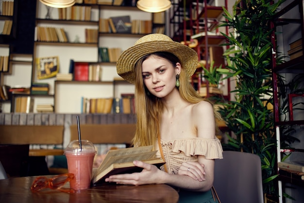 Pretty woman in hat with book in hands reading vacation in cafe.