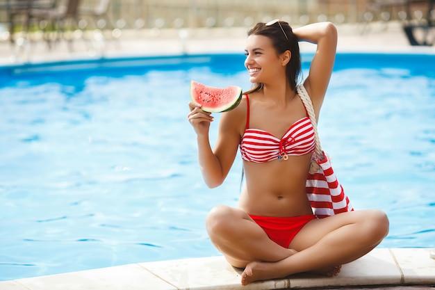 Красивая женщина, имеющая естественный загар возле бассейна.