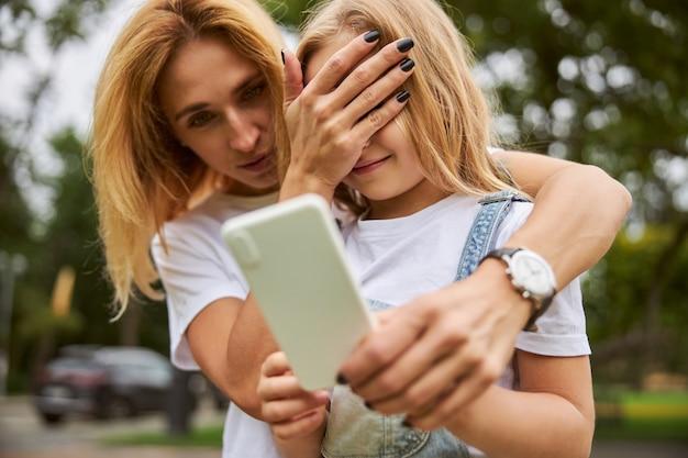 여자 아이가 야외에서 손에 휴대 전화를 들고있는 동안 예쁜 여자는 어린 소녀와 재미