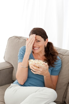 Pretty woman hiding her face while watching a horror movie