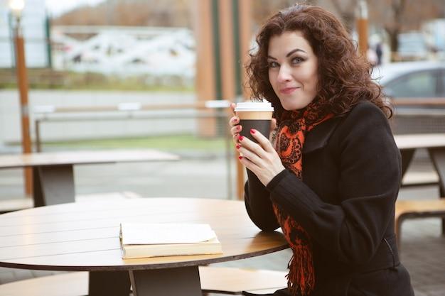 ホット濃いコーヒーのカップを保持しているきれいな女性