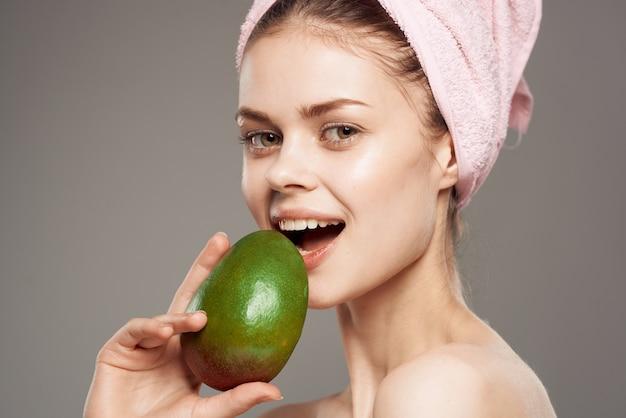彼女の手にマンゴーを持っているきれいな女性彼女の頭にピンクのタオル