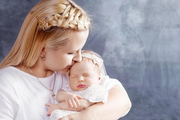 彼女の腕の中で生まれたばかりの女の赤ちゃんを保持しているきれいな女性。