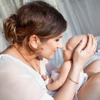그녀의 팔에 갓 태어난 아기를 들고 예쁜 여자