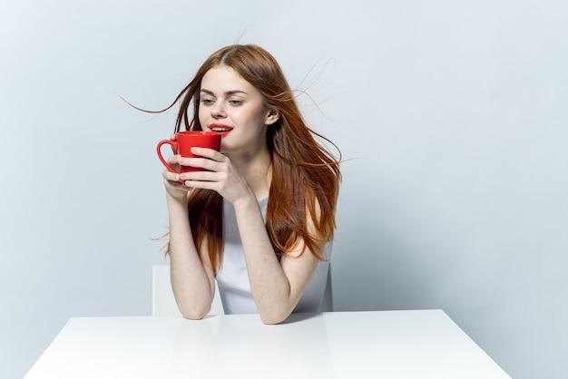 Красивая женщина держит в руке красную кружку, сидя за кофейным столиком