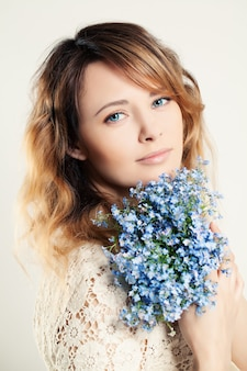 Pretty woman holding blue flowers