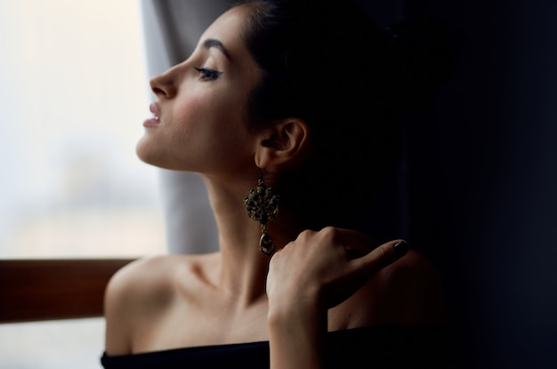 Pretty woman holding a camera near the window decoration fashion fashion model. high quality photo