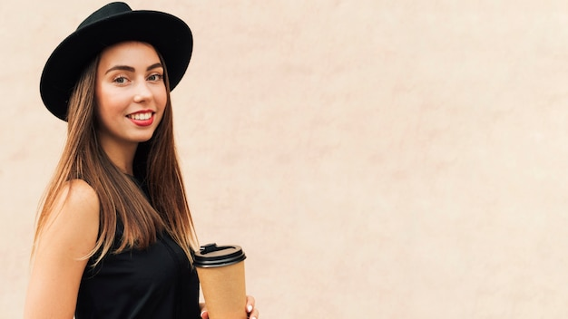 Pretty woman holding a cup of coffee with copy space