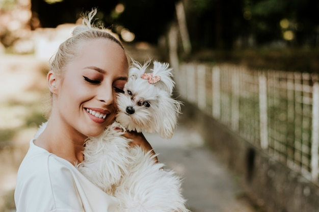 Pretty woman holding a cute, small maltese dog.