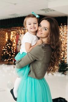 娘を手に持って、モミの枝と明るい花輪の装飾されたスタジオに立っているきれいな女性