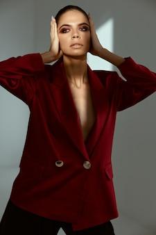 顔化粧品赤いジャケットモデルを保持しているきれいな女性