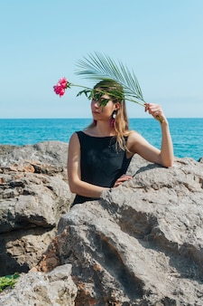 Pretty woman holding flower and palm leaves leaning on rock near sea