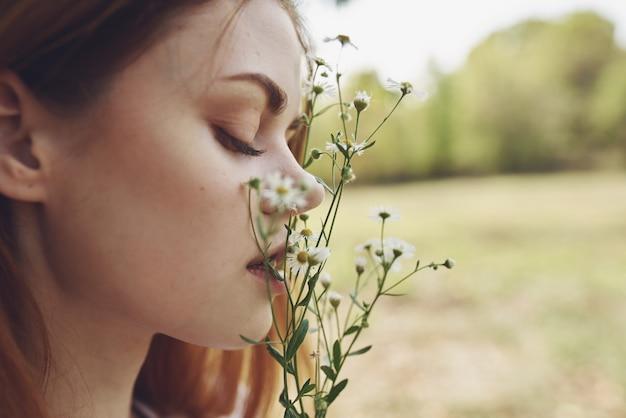 花を持っているきれいな女性ライフスタイルの夏。高品質の写真