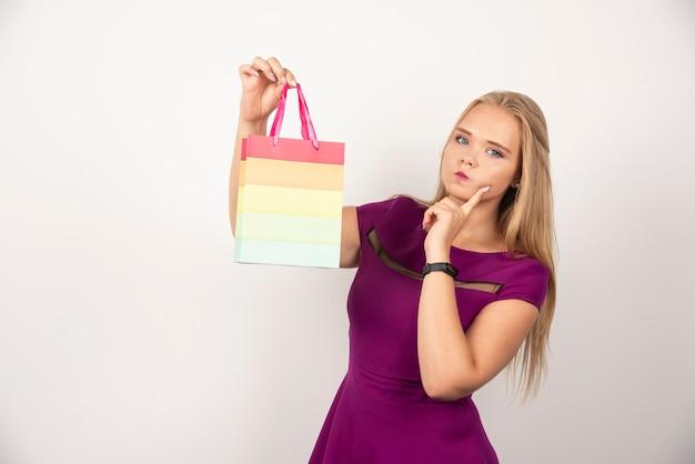 선물 가방을 들고 생각하는 예쁜 여자.