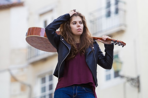 Pretty woman holding guitar on shoulder on street
