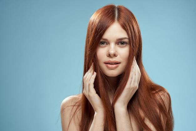 Красивая женщина, держащая волосы в руках, ухаживая за обнаженными плечами, обрезала вид на синем фоне.