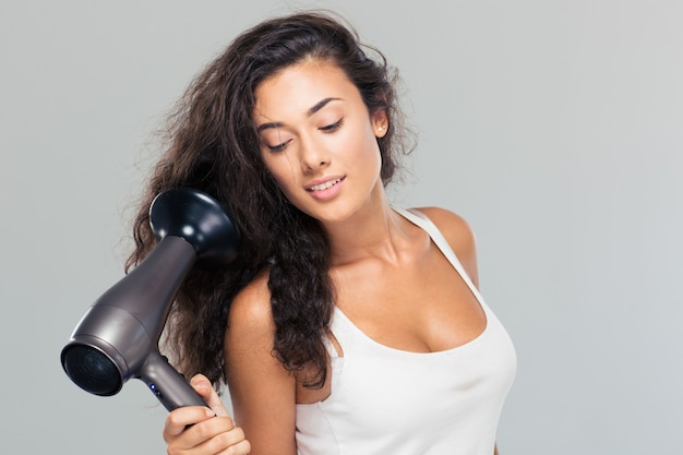 Pretty woman holding hairdryer