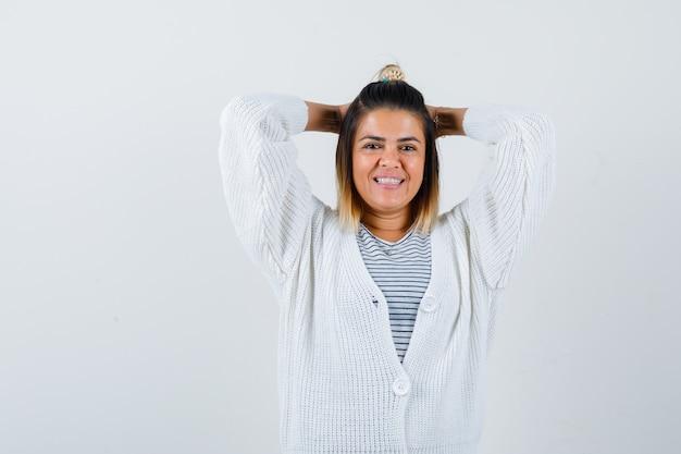 Красивая женщина держит руки за головой в футболке, кардигане и выглядит весело